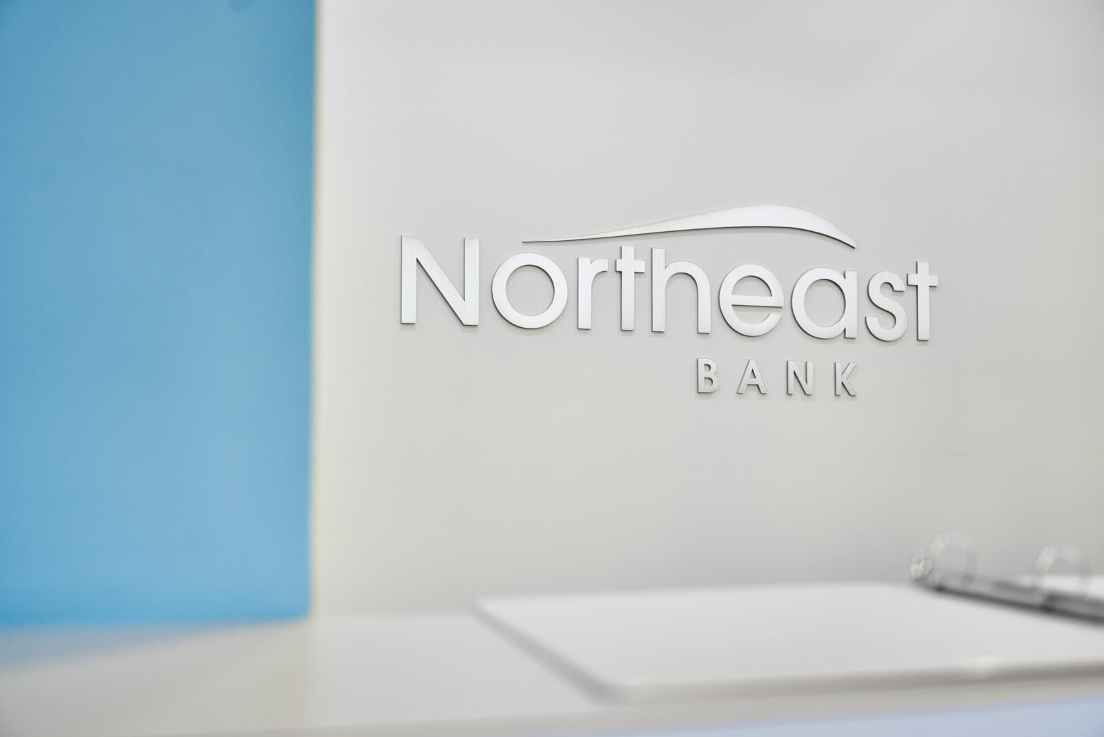 Northeast Bank logo mark on white wall